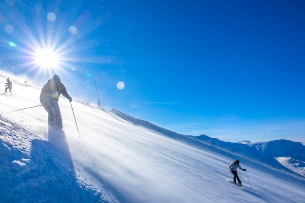 Sunny weather at the ski resort. a strong wind blows snow down a steep slope. multiple skiers