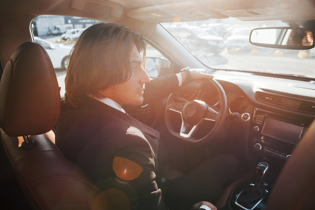 Sunny weather. young businessman in black suit and tie driving modern automobile.