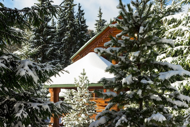 Sunny winter day in forest. wooden cottage or chalet covered with snow. ski and snowboard resort, winter vacations outdoors.