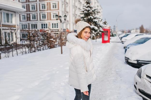 雪でいっぱいの通りを歩いて素晴らしいきれいな女性の晴れた冬の朝。