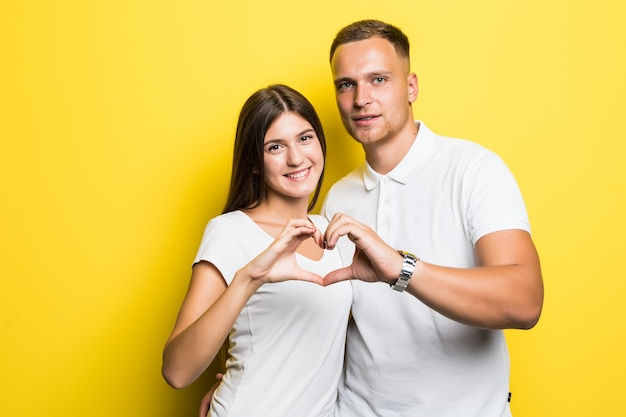 La giovane coppia piena di sole in magliette bianche mostra il segno del cuore con le loro mani isolate