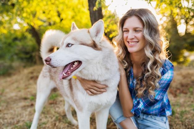 Солнечная молодая стильная довольно улыбающаяся счастливая блондинка играет с собакой породы хаски в парке в солнечный летний день