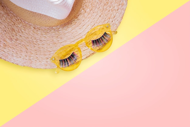 Sunprotection objects. straw woman's hat with sun glasses and fake eyelashes top view bright yellow background flat lay single.
