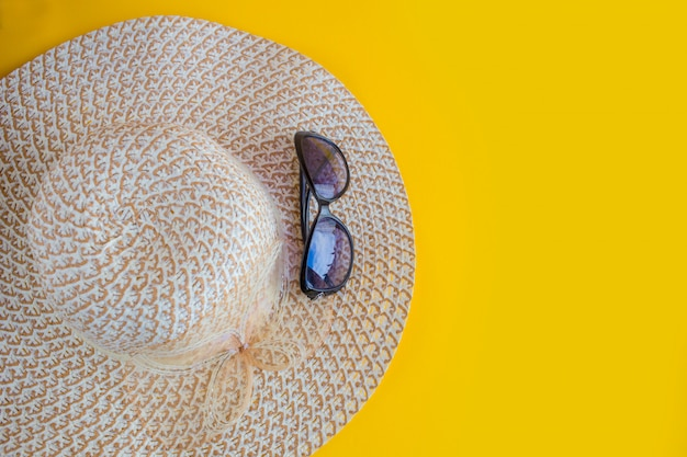 Sunprotection objects. straw woman's hat with yellow sun glasses top view bright yellow background flat lay. beach accessories. summer travel vacation concept. copy space
