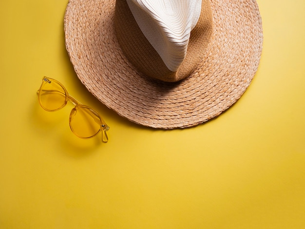 Sunprotection objects. straw woman's hat with yellow sun glasses on view yellow