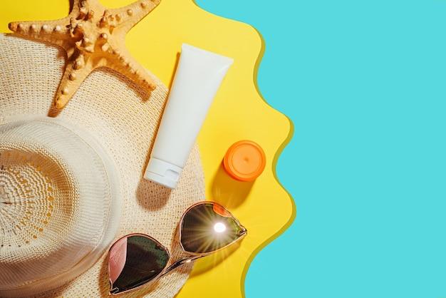 日焼け止めオブジェクト、日焼け止め。サングラスと保護クリームspfフラットとわらの女性の帽子は黄色の背景に横たわっていた。ビーチアクセサリー。夏の旅行休暇の概念