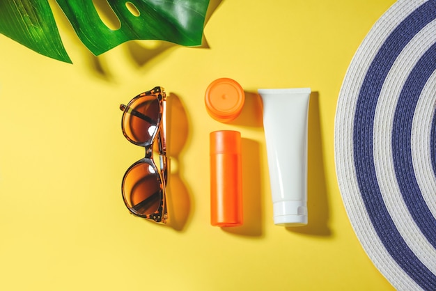 日焼け止めオブジェクト。サングラスと保護クリームspfフラット女性の帽子は黄色の背景に横たわっていた。ビーチアクセサリー。夏の旅行休暇の概念