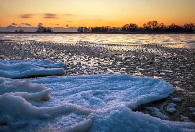 일출과 얼어 붙은 강. 아침 시간에 호수와 아름 다운 겨울 풍경입니다. 새벽