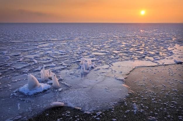 일출과 얼어 붙은 바다. 아침 시간에 호수와 아름 다운 겨울 풍경입니다. 새벽