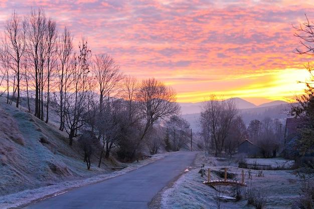 最初の秋の霜のある日の出と山の村の道