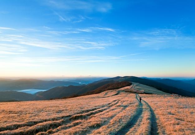 田舎道と観光客がいる日の出カルパティア山脈(ウクライナ)の秋の風景。