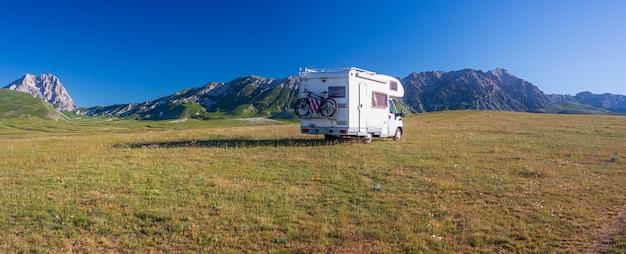 Восход солнца ясное голубое небо над автофургоном в высокогорье кампо императоре, абруццо, италия. уникальный пейзаж нагорья и скалистых гор, альтернативная концепция отдыха vanlife.