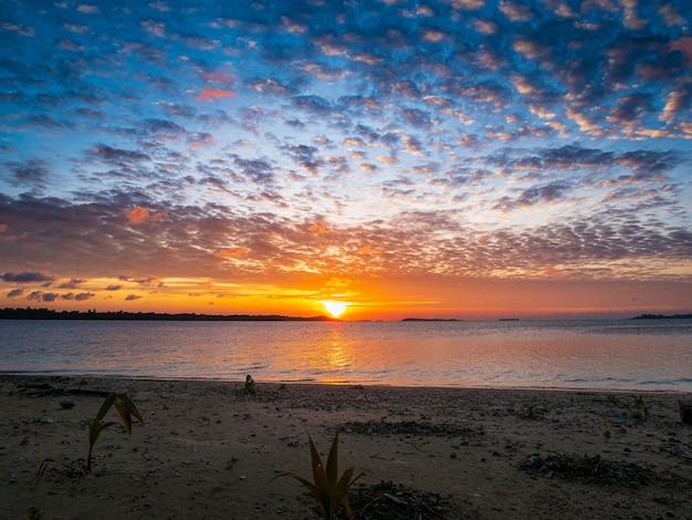 海、熱帯の砂漠のビーチ、ない人、嵐の雲の日の出の劇的な空