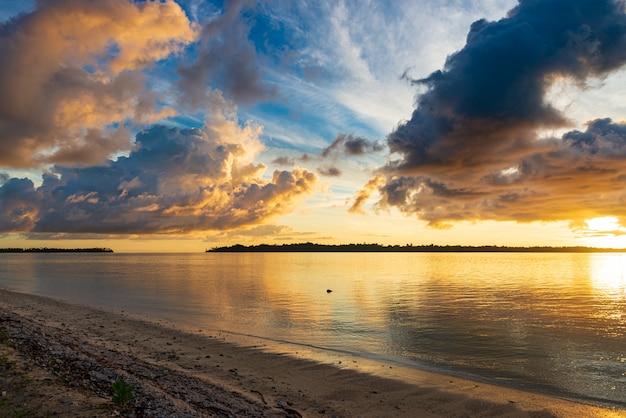 海、熱帯の島、独特の嵐の雲、金色の日光の日の出の劇的な空