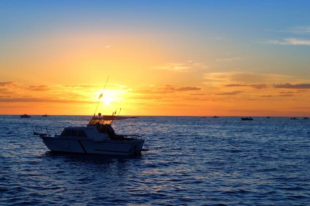 日の出釣り船青い海、オレンジ色の空