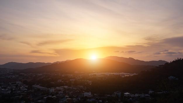 日の出は、熱帯の国のタイムラプスで小さな町と森のある谷を囲む丘に沈む夕日になります