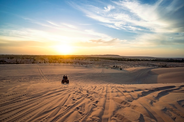 砂漠の日の出。 2人のatvバイカーがいるシーン。観光客はベトナムの砂漠の砂丘を通ってオフロードatvに乗ります。ムイネーベトナムの早朝のサファリ。