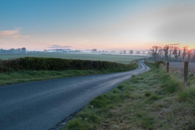 Восход солнца в ирландии, пейзажная фотография загородной местности с голубым небом и туманом над горизонтом.