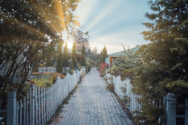 コテージと庭園の間の小さな村の歩道の日の出道路の周りの小さな柵美しい家...