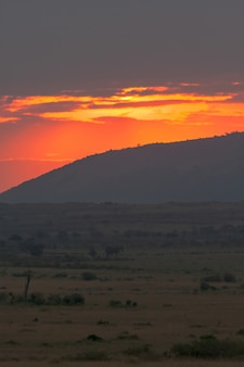 雲の日の出。ケニアマサイマラのサバンナ