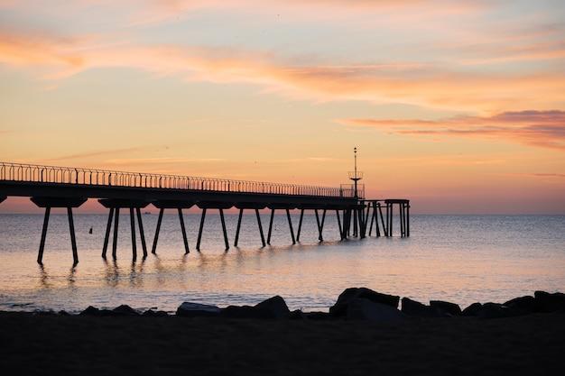ポンツーンとビーチポンデルペトロリバダロナバルセロナカタルーニャスペインを望む地中海の日の出