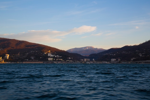 海の街と地平線ソチの山々に昇る太陽のピンクの霞の海の日の出...