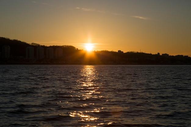 海の昇る太陽の海のピンクの霞の日の出。地平線上の都市と山。新しい日の始まり