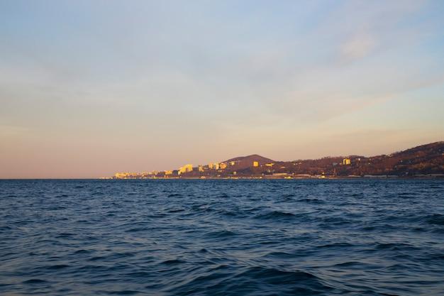 海の街と地平線上の山々に昇る太陽のピンクの霞の海の日の出