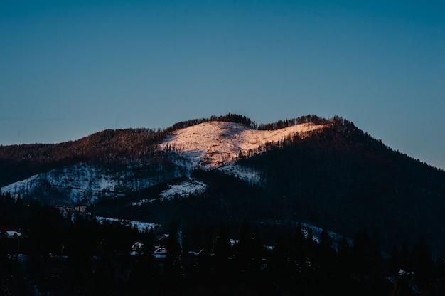 冬の山の日の出。山の中の雪に覆われたスキー場。テキストの場所。冬の休暇と休日の概念。
