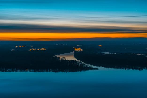 夜明け前の空の下に森のある川と島のある日の出の風景