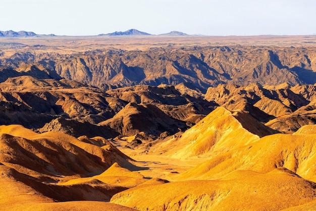 일출은 yellow moon 계곡을 비춥니다. 아프리카의 사막 풍경. 나미비아