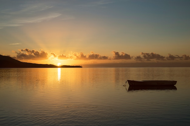 Sunrise in mauritius with the sun in the background and a fishing boat in the foreground