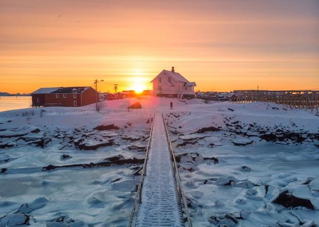 Sunrise over nordic house and wooden bridge on coastline in winter at lofoten islands, norway