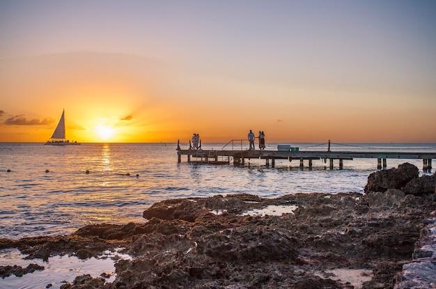 Восход солнца на пирсе в море в байяибе, доминиканская республика