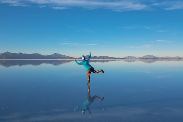 볼리비아의 salar de uyuni에 일출 물, 소금 평평한 사막과 하늘 반사에 여자 관광으로 덮여
