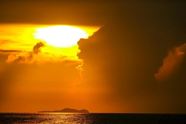 Восход солнца на силуэте облака неба рыбацкой лодке и на море остров