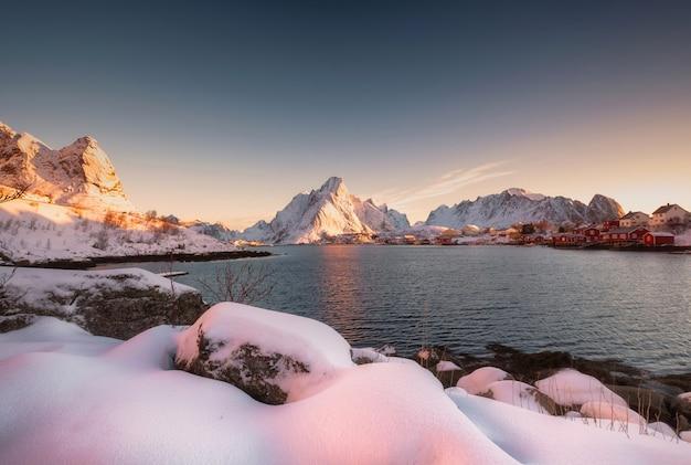 ノルウェー、ロフォーテン諸島の海岸線の冬のレーヌ村の雪の日の出