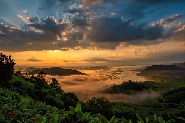 山の谷から昇る朝日。自然の夏の風光明媚な設定で川の近くの緑の谷の美しい画像。水の近くの美しい日。朝の霧は穏やかな雰囲気を作り出します。