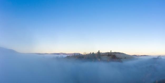 Восход солнца над горными холмами, покрытыми серым туманом.