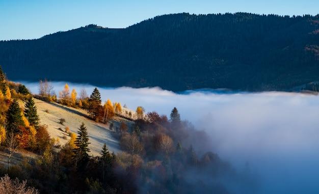 Восход солнца над горными холмами, покрытыми серым туманом