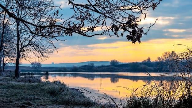川の日の出、朝の岸の川の霜に覆われた草、川の空の反射