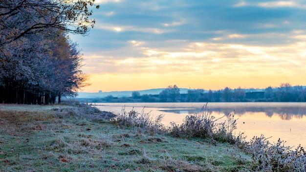 凍えるような朝、川から昇る朝日。朝の川岸の霜に覆われた木々や草