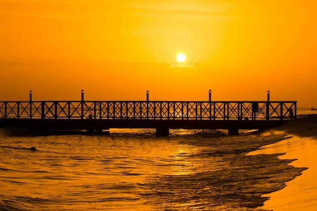 海から昇る朝日。手前の桟橋。パノラマ