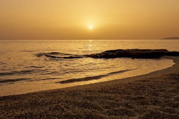 Восход солнца над тропическим морем на крите с волнами, ударяющими по песку.