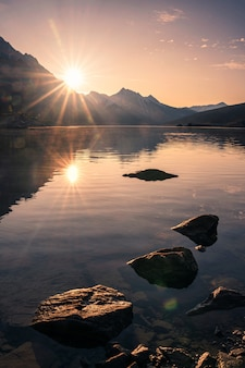 Sunrise on rocky mountain with rocks in medicine lake at jasper national park