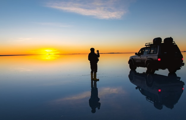Sunrise on salar de uyuni in bolivia covered with water, car and man in salt flat desert and sky reflections
