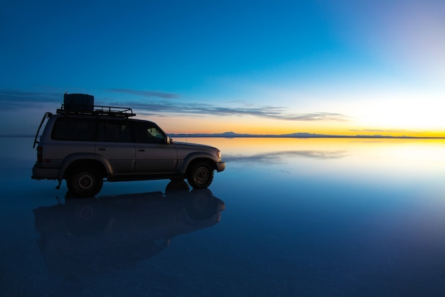 Sunrise on salar de uyuni in bolivia covered with water, car in salt flat desert and sky reflections