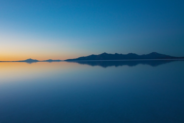 Sunrise on salar de uyuni in bolivia covered with water, salt flat desert and sky reflections