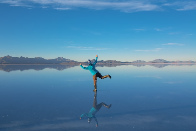 Sunrise on salar de uyuni in bolivia covered with water, woman tourist on salt flat desert and sky reflections