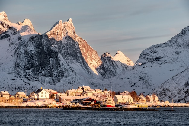 Sunrise on scandinavian village with snow mountain background on coastline
